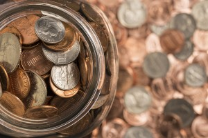 A collection of coins in a glass jar surrounded by coins.